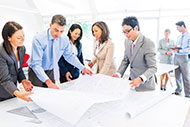 Architects having meeting around table with blueprints