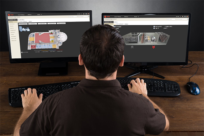 a worker sitting in front of monitors with Trane software running