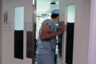 Surgeon opening operating room door