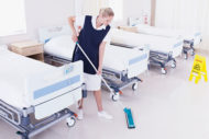 Environmental services technician cleaning floor