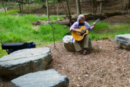 Man playing guitar on Green Road wild garden at Walter Reed Medical Center