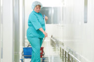 Environmental services worker cleaning floor