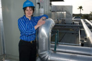 Woman engineer standing next to rooftop chiller