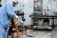 Technician cleaning OR floor