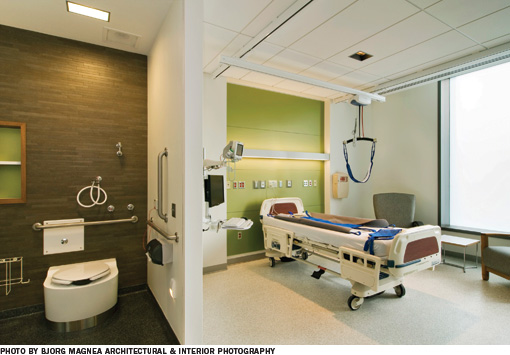 Hospital room with a bedroom on the right, and bathroom on the left, with a wall dividing them