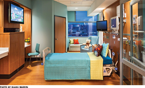 A colorful children's hospital room.  The walls and bed are teal with yellow accents.  There is extensive wood paneling on the walls and a teddy bear sits on the chair.