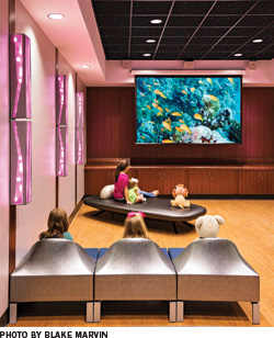 Children sit in a colorful theater room and watch a movie.