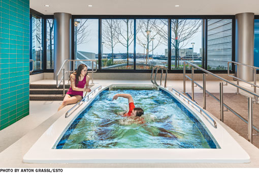 A physical therapist sits next to a therapy pool as a patient performs physical therapy exercises in the water