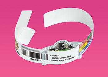 A hospital patient bracelet with additional electronics attached to it.