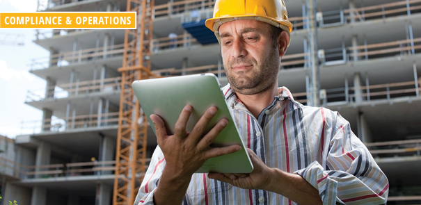 Man at construction site looking at tablet